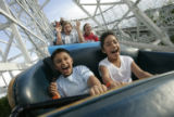 Jaylon Torrez (cq), 9, left, and cousin Angelic Torrez (cq), 9, enjoy a ride on The Cyclone with...
