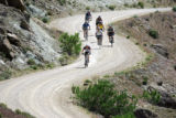 Cary Smith (cq, out front of pack), 43,  of Littleton leads a group of riders down an access road...