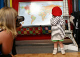 Ashley Martinez, 3, of Denver shies away from the camera held by Julie Busboom (cq) as she wears a...