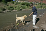 Ryan Rambo (cq), 8,right, give Zion, a yellow Labrador retriever a treat along the banks of the...