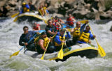 Members of the Denver Rescue Mission's New Life program negotiate the Zoom-Flume rapids as they...