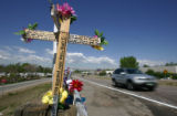 A cross and flowers mark the site where three persons were killed in a car accident on Monday...