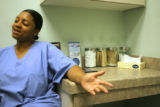 Ronique Brown (cq), 24, of Denver talks about her lower back pain at the NextCare Urgent Care...