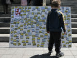 Matt Robinson,  4, of Engelwood checks out a board of names of citizens who have pledged to join...