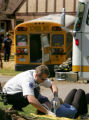 A paramedic treats a victim after a school bus transporting children from Hill Middle School ran...