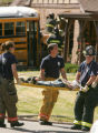 Paramedics and Fire personnel transport an injured child after a school bus transporting children...