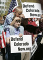 Kathleen LeCrone (cq) holds her son, Spencer,6  on her shoulders during a rally for Defend...
