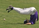 "Fort Collins' right fielder Garrett Houts tumbles ""heels over head"" as he drops a fly..."