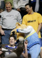 Denver Nuggets mascot Rocky uses hair clippers to shave a Los Angeles Clippers fan in the second...