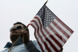 Edmundo Barajas (cq) a Fort Collins stands with his American flag while listening to a speaker in...