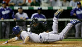 Starting pitcher Brett Tomko slides past the tag by Rockies catcher Danny Ardoin in the top of the...