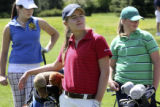 Kayley Kempton, center foreground red shirt, B hat, leans on her bag at the tee box waiting for...