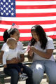 Mary Zavala, 17, (cq) (l), who is holding her cousin Omar Morquecho (cq), 1, and her friend...