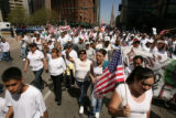 Marchers turn on to Broadway as they approach the state Capitol. Marchers began a pro-immigrant...