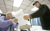 (Estes Park shot on 3/22/05) Election Judge Rich Smith (left) helps voter Frank Theis(CQ-Frank...