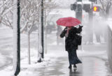 Qwest employee Wendy Johnson (cq) tries to hold on to her umbrella iin the blowing snow as she...