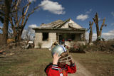 MJM555  Michael Kidnigh (cq), tries on a football helmet outside a friends damaged home in Holly,...