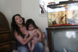 38 year-old Marie Gomez talks to reporters at her home in Louisville, as her 5 year-old son and 1...