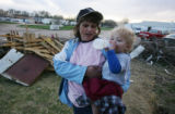Chantel Fuller (cq), 31, holds her son Brendyn Fuller (cq), 3, amidst the wreckage in Holly,...