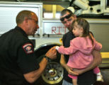 Fireman A J Johansen (cq), left,  greats Robert Lynch, who is holding his two year old daughter...