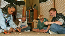 Spelling coach Natalie McGowan (cq) plays speed scrabble with Alec Smith, 10, Zack Smith, 14, and...