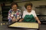 Mary Rotola, (cq), 93, left, and lifelong friend Lucille Acierno (cq), 83, work on honey cookies,...