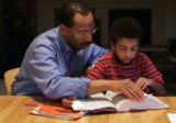 Peter Chapman helps his son, Evan, 10, look up a word in the dictionary for his homework on March...