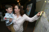Jessica Williams (cq), holds her son Matthew, 4, while pointing to her sticker in a map as the...