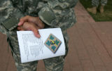 Command Sgt. Major Ricky Buchanan (cq) holds a program with a memorium on the back for soldiers...