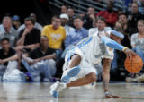 Denver Nuggets guard Allen Iverson balances himself with one hand after being fouled in the first...