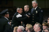 Aurora Officer Gary Rivale is consoled by fellow officer with Deputy Chief Terry Jones standing by...