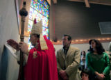 Bishop Robert Shaheen, annoints and blesses the walls of the church during the Dedication and...