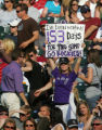 "A fan holds a sign saying ""I've been waiiting 153 days for this game. Go Rockies"" at the..."
