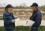 Patricia Gray, left, and Martin McNeese, of FEMA look at a home during a Preliminary Damage...
