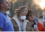 (from left) Chad Wright (cq), Jan Wright (cq) and Melody Hart (cq) look on, as a crew tears down...