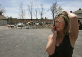 Dee Ann Burns talks on her cellphone, as she reviews the damage that her friend's home sustained...