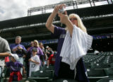 Jenna Briggs (CQ) gets a photo of Colorado Rockies first baseman Todd Heltson, as hundreds of fans...