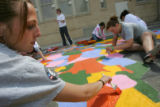 AmeriCorps volunteers paint the playground at Fairview Elementary School in Denver on Sunday,...