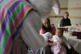DLM6315  Eight-month-old Alex Thisted gets a visit from the Easter Bunny as she sits on the lap of...
