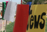 A series of signs posted on campus adjacent to a field of flags representing those killed in the...