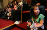 Sienna Reyes (cq), 5, holds a picture of her father, Sgt. Luis Reyes (cq), in the State Senate as...