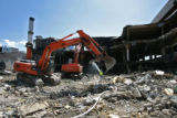 Water is sprayed to keep down the dust, as demolition excavators works on taking down the...