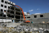 A high reach demolition excavator works on taking down the old Rocky Mountain News building,...