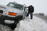 DLM2690  Tracy McKee tries to dig his SUV out after getting it stuck on the southbound shoulder of...