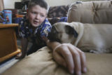 Jerry Monfelt, 10, (cq), gives Missie his arm to rest her head upon on the couch in the family...