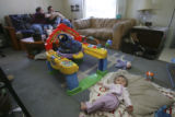 Trinity Monfelt, 10 months, plays in blissful ignorance of the death behind her as Stephanie...