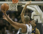 The San Antonio Spurs forward Tim Duncan, left is guarded by Denver Nuggets Marcus Camby in the...