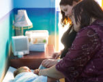 Tracey Ruiz reviews a swaddling technique to soothe 8-month-old Tobias Vilain for his mother,...