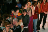 Designer Armando Guerra (Cq), in black jacket and glasses, reacts with model Chelle Kay, (Cq)...