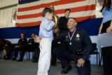 DLM5660  Officer Jim Dixon laughs as his son Caiden, 4,  puts on one of  the medals he was...